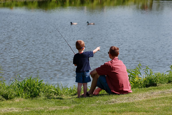 Young boy fishing with his father.
