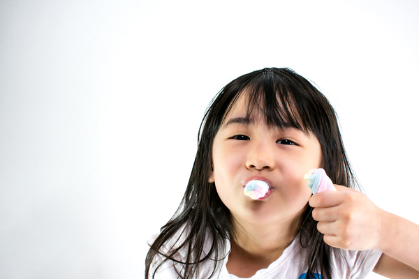 Child eating two marshmellows
