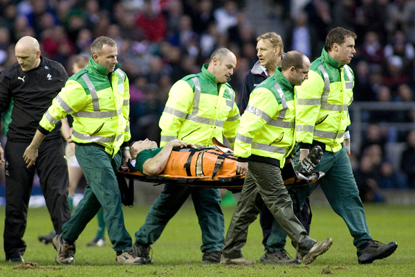 Rugby Union player getting taken from the field on a stretcher.